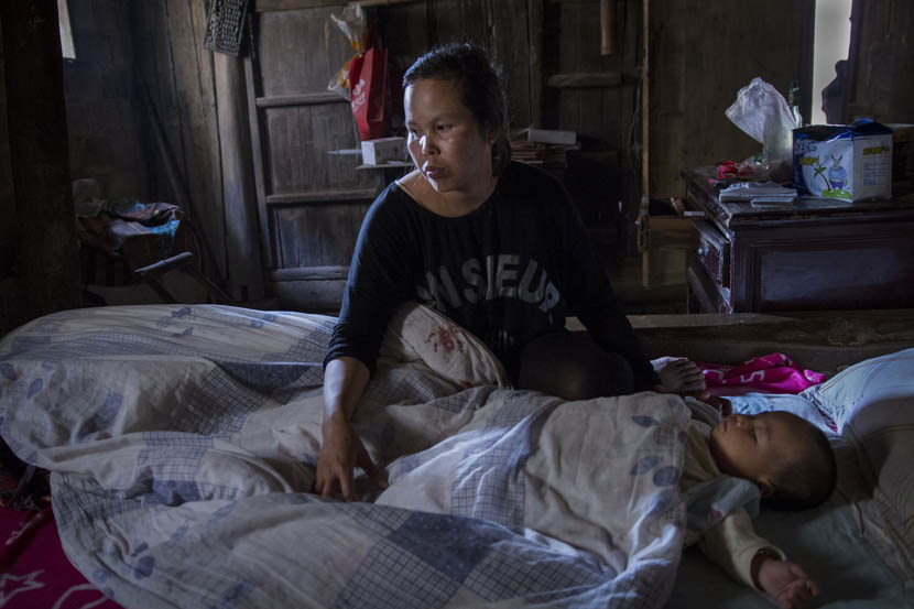 Buntha sits next to her sleeping baby in the morning in Huanggang Town, Jiangxi province, June 2015. She has to take care of the baby and do housework mainly on her own, because her husband works long hours. Courtesy of Cong Yan