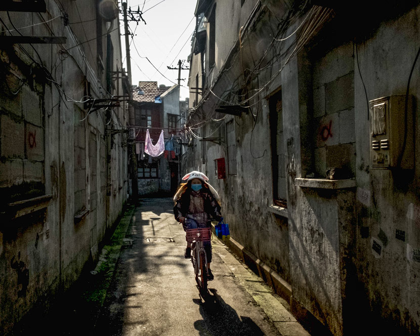 A young woman rides along an alley in Laoximen, Shanghai, Jan. 17, 2019. Daniel Holmes/Sixth Tone