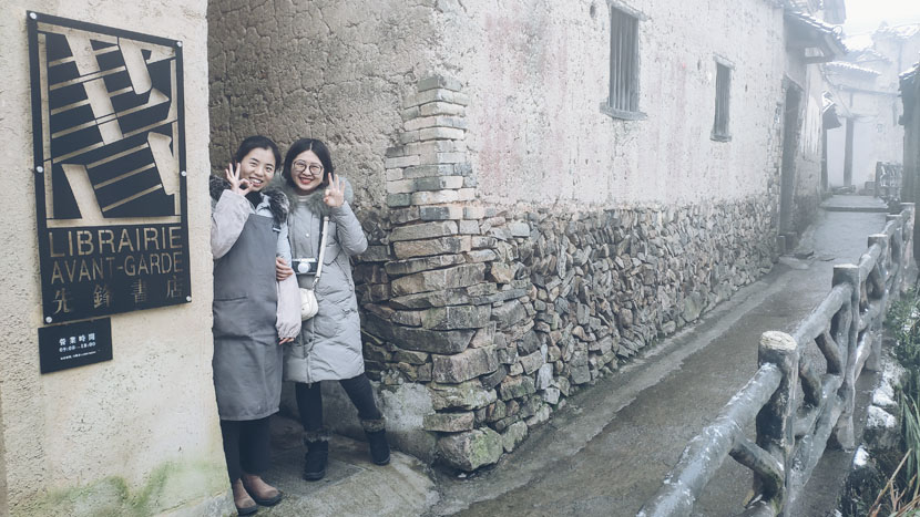 Li Xia, the store manager (left), and a reader pose for a photo next to Chenjiapu Bookstore in Songyang County, Zhejiang province, Jan. 2, 2019. Fan Yiying/Sixth Tone