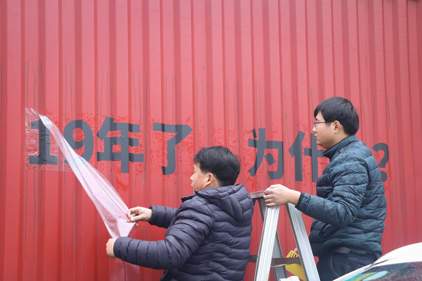 "Employees of a print shop apply ""For 19 years, why?"" onto a truck in Shanghai, Jan. 11, 2019. Yin Yijun/Sixth Tone"