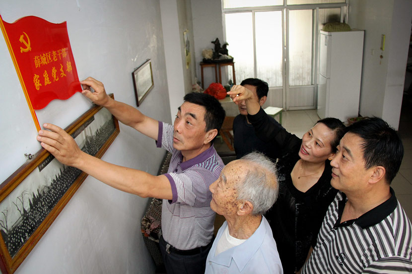 "A Party member hangs a ""Party Family Branch"" sign in a community activity room in Zaozhuang, Shandong province, June 29, 2012. VCG"