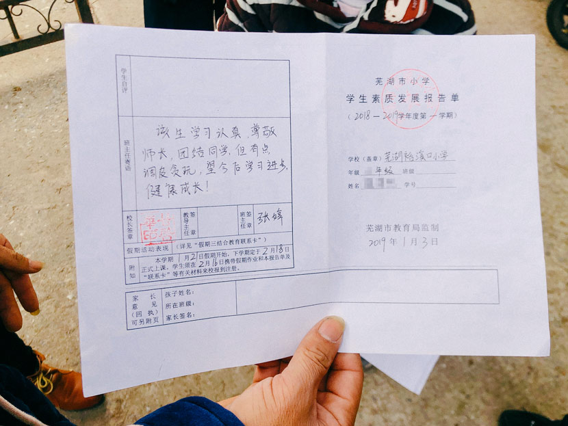 A parent shows his child's school report in Wuhu City, Anhui province, Jan. 20, 2019. Fu Danni/Sixth Tone
