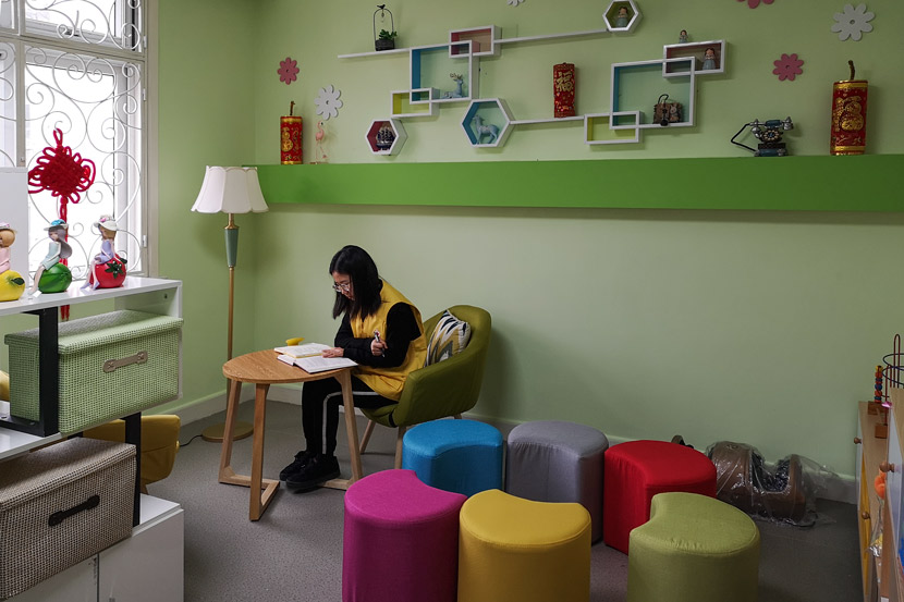 A volunteer reads a book in an activity room designed for counseling sessions for families of hospice patients at Chengjiaqiao Community Health Service Center, Shanghai, March 5, 2019. Ni Dandan/Sixth Tone