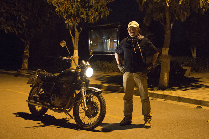 Xu Song poses for a photo with his motorbike in Dali, Yunnan province, March 16, 2019. Shi Yangkun/Sixth Tone