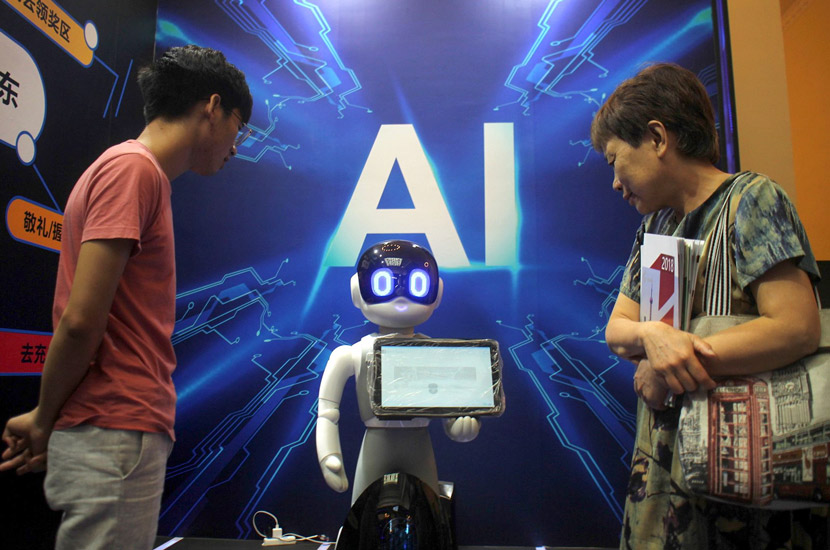 Visitors examine a robot during a popular science product expo in Shanghai, Aug. 27, 2018. Xing Yun/VCG