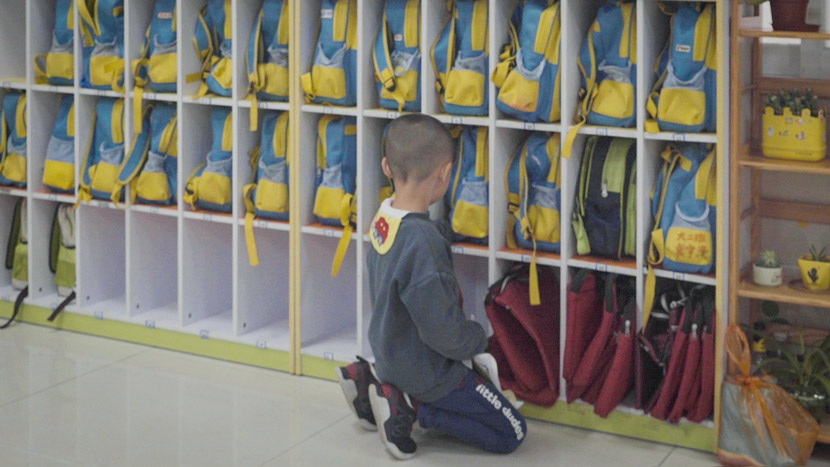 A child looks at shelves of backpacks in Dongguan, Guangdong province, March 25, 2019. Liu Jingwen/Sixth Tone