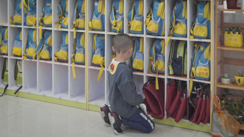 A child looks at shelves of backpacks in Dongguan, Guangdong province, March 25, 2019. Liu Jingwen/Sixth Tone