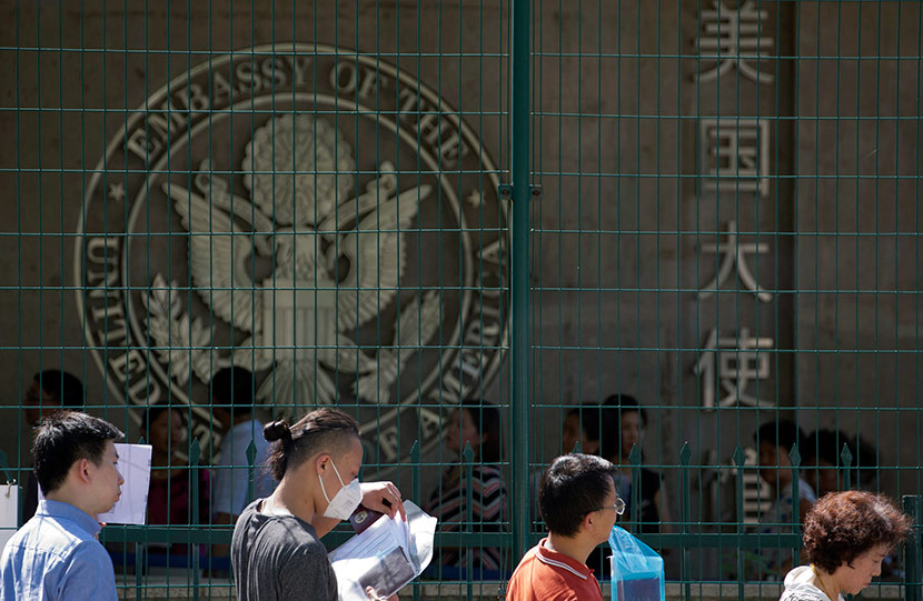 Visa applicants wait to enter the U.S. Embassy in Beijing, July 26, 2018. Ng Han Guan/IC