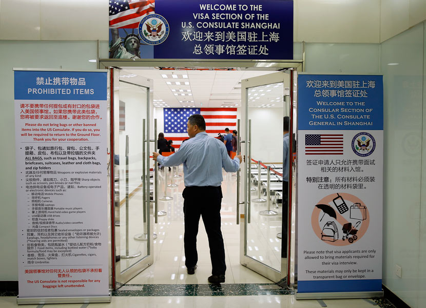 An employee opens the door to the visa section of the U.S. Consulate in Shanghai, Sept. 16, 2015. VCG