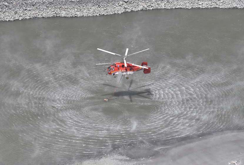 A rescue helicopter fetches water to put out a deadly forest fire that killed 27 firefighters and three people from the local fire department in Muli County, Liangshan Yi Autonomous Prefecture, Sichuan province, April 2, 2019. Liu Kun/Xinhua
