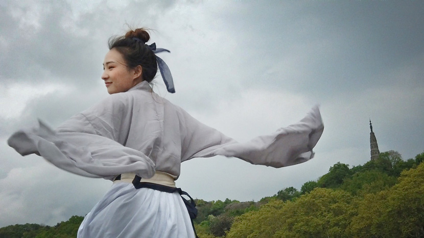 A woman in traditional Han clothing waves her arms on a windy day in Hangzhou, Zhejiang province, April 9, 2019. Yang Chaobo/Zhejiang Daily Press Group/IC