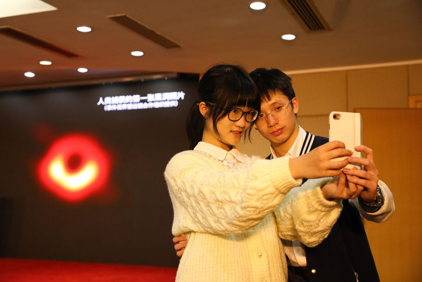 Students from the Chinese Academy of Sciences take selfies with the first-ever image of a black hole while attending a press conference in Shanghai, April 10, 2019. Jiang Xiaowei/IC
