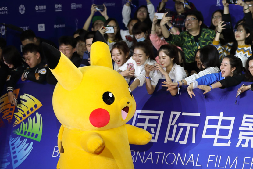 Visitors play with Pikachu during the 9th Beijing International Film Festival in Beijing, April 13, 2019. Song Fan/IC