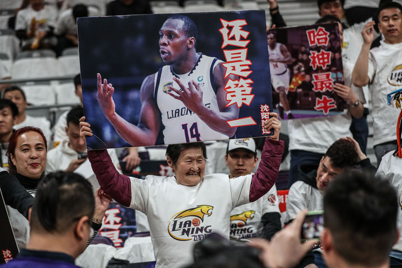An elderly fan raises a sign in support of one of her team's stars during a CBA match in Shenyang, Liaoning province, April 9, 2019. Pan Yulong/Xinhua