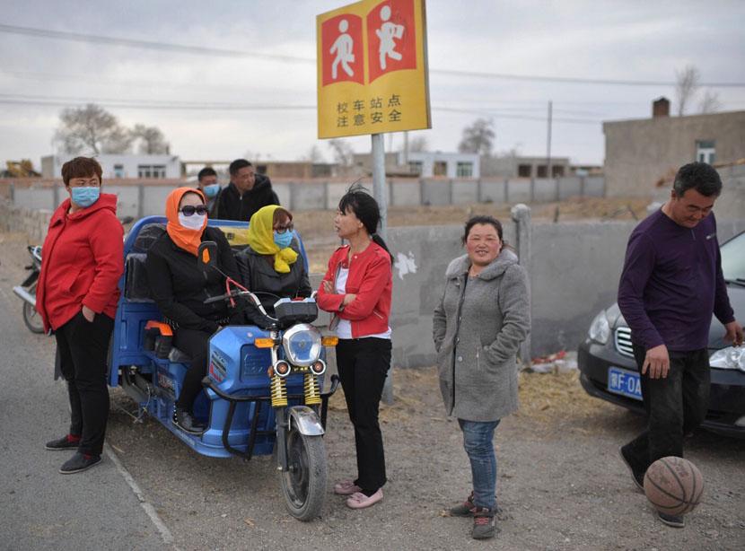Parents wait for the school bus to drop their children off in Hinggan League, Inner Mongolia Autonomous Region, April 12, 2019. Cui Nan for Sixth Tone