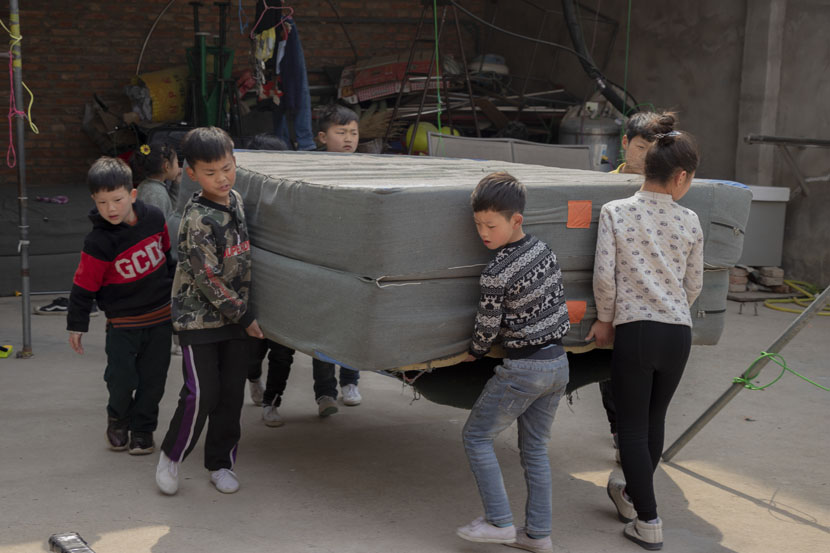 Children move mats in Bozhou, Anhui province, March 22, 2019. Kenrick Davis/Sixth Tone