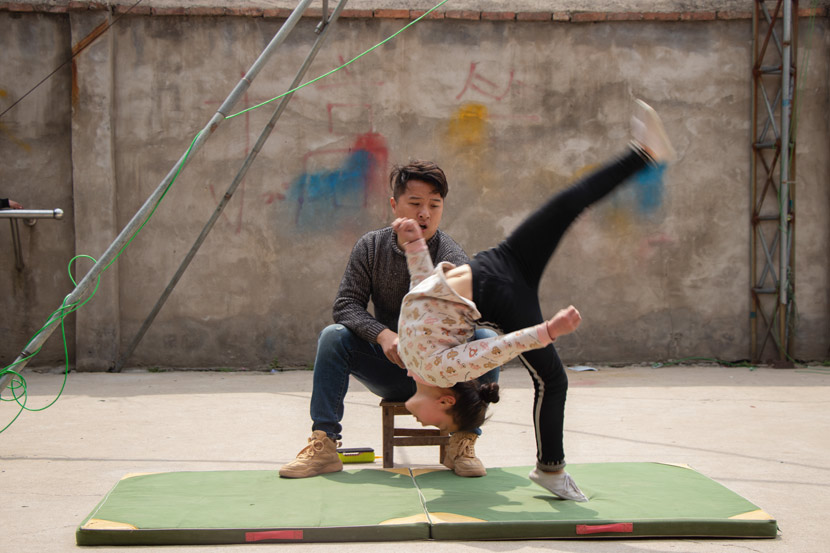 Li Xiaogao watches a girl practice her tumbling in Bozhou, Anhui province, March 23, 2019. Kenrick Davis/Sixth Tone