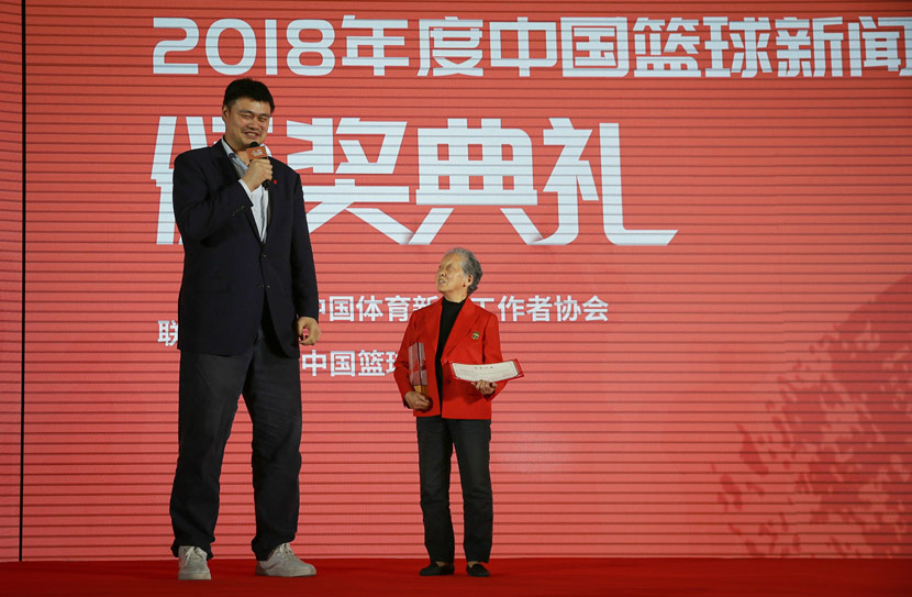 Yao Ming (left) speaks as 81-year-old sports photographer Hong Nanli (right) receives a special award for her basketball reporting contributions during the China Basketball News Award ceremony in Beijing, April 24, 2019. IC