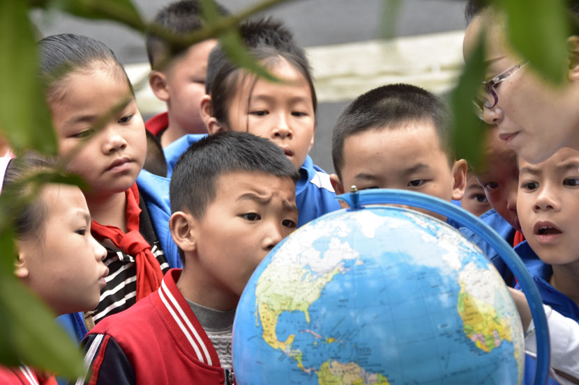 Students look at a world globe on Earth Day at a primary school in Congjiang County, Guizhou province, April 22, 2019. Luo Jinglai/Xinhua