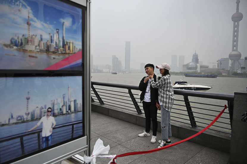 A couple pose for a photographer on the waterfront of the Bund along the Huangpu River during a May Day holiday in Shanghai, May 1, 2019. Hector Retamal/AFP/VCG