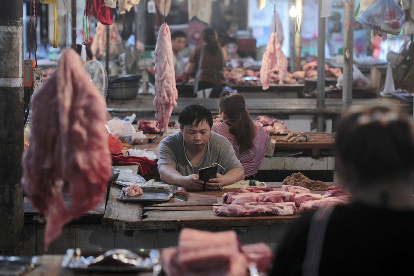 A vendor looks at an electronic device in a meat market in Hekou Yao Autonomous County, Yunnan province, May 3, 2019. Wong Campion/Reuters/VCG