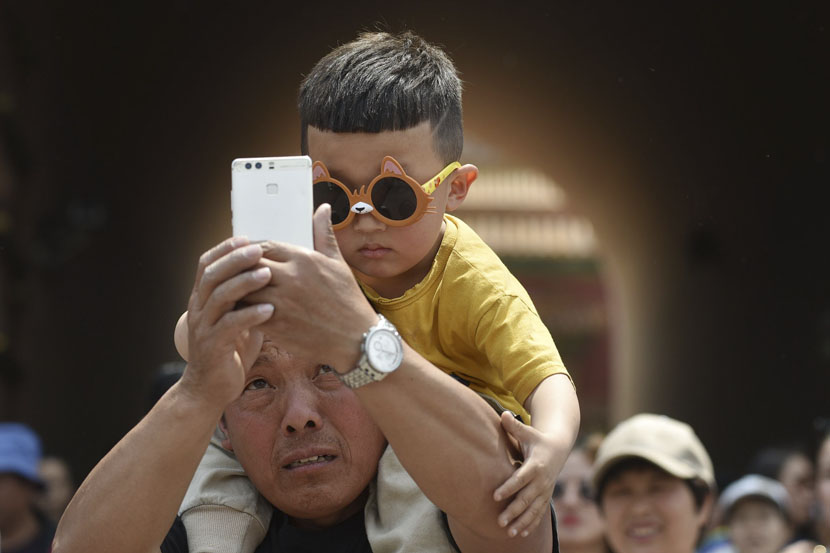 A man takes a selfie with a young boy near the Forbidden City palace complex in Beijing, May 3, 2019. Greg Baker/AFP/VCG