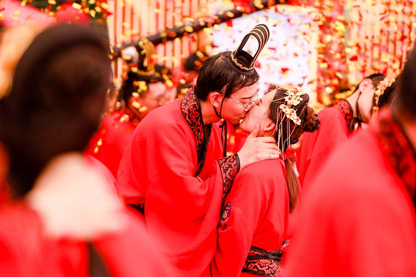 Two people kiss during a mass wedding ceremony at the headquarters of tech giant Alibaba in Hangzhou, Zhejiang province, May 10, 2019. The ceremony featured 102 couples, each with at least one person employed by Alibaba. VCG