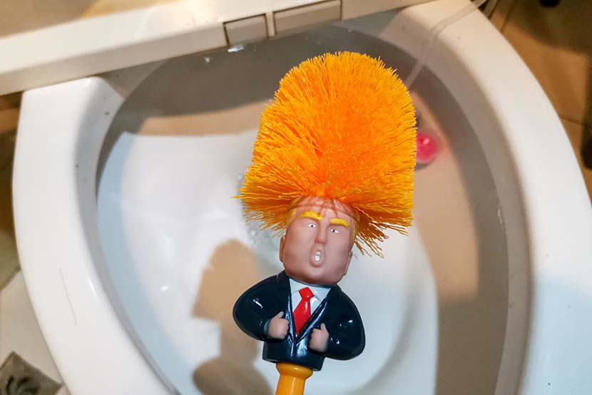A local resident shows off a toilet brush that features U.S. president Donald Trump at his home in Shanghai, May 15, 2019. IC