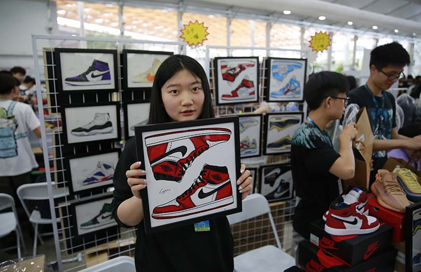 Lin Lihui, a student who creates sneaker-themed art, poses for a photo in her booth at Sneaker Con Shanghai, May 17, 2019. Kenrick Davis/Sixth Tone