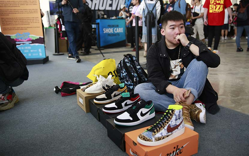 Zhang Xinlie, a collector who owns around 1,000 pairs of sneakers, sits in front of five pairs of shoes he's hoping to sell at Sneaker Con Shanghai, May 17, 2019. Kenrick Davis/Sixth Tone