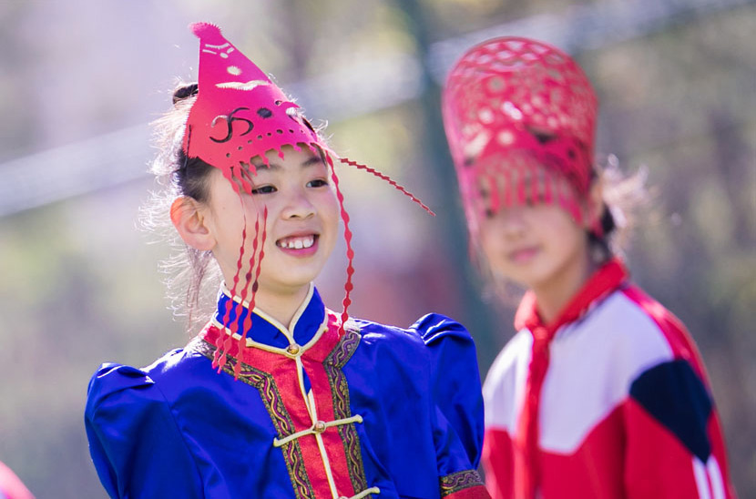 A student in traditional garb and paper-cut headgear poses for a photo at a primary school in Hohhot, Inner Mongolia Autonomous Region, May 21, 2019. Ding Genhou/IC