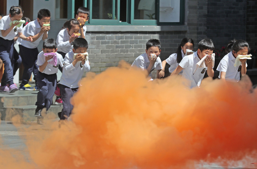 Pupils cover their mouths during a fire drill at a school in Hangzhou, Zhejiang province, May 24, 2019. Zhejiang Daily Media Group/IC