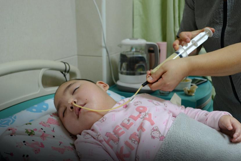 Liu Xuejie feeds Niuniu with a syringe at a hospital in Guangzhou, Guangdong province, April 14, 2019. Fan Liya/Sixth Tone