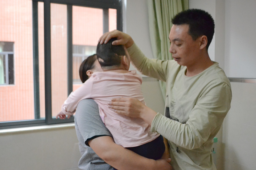 Zhang Shaofeng helps Niuniu loosen mucus by patting her on the back at a hospital in Guangzhou, Guangdong province, April 14, 2019. Fan Liya/Sixth Tone