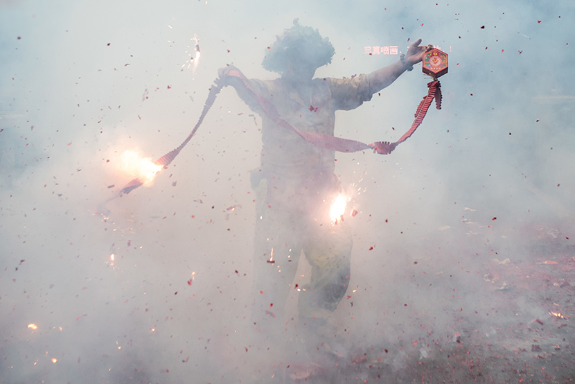 A man holds a lit firecracker while celebrating the Dragon Boat Festival holiday in Guangzhou, Guangdong province, June 6, 2019. IC