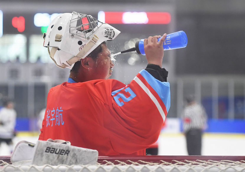A hockey player sprays water on his face to cool off during a match in Beijing, June 5, 2019. Jia Yuchen/Xinhua