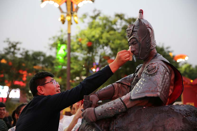 A tourist wipes sweat off an actor dressed as a terra cotta warrior in Xi'an, Shaanxi province, June 13, 2019. Wei Yongxian/VCG