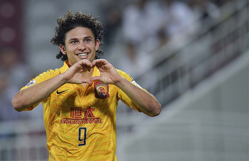 Brazilian soccer player Elkeson makes a heart sign to fans during an AFC Champions League match in Doha, Qatar, Sept. 18, 2013. VCG