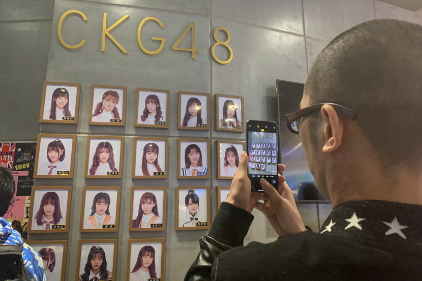 A fan takes a picture of the portraits of CKG48 members in Chongqing, March 16, 2019. Yin Yijun/Sixth Tone