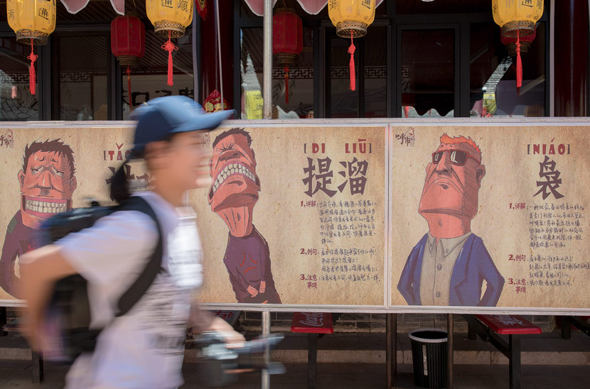 A woman walks past posters of an exhibition about the city's local dialect in Hohhot, Inner Mongolia Autonomous Region, May 23, 2019. Ding Genhou/VCG