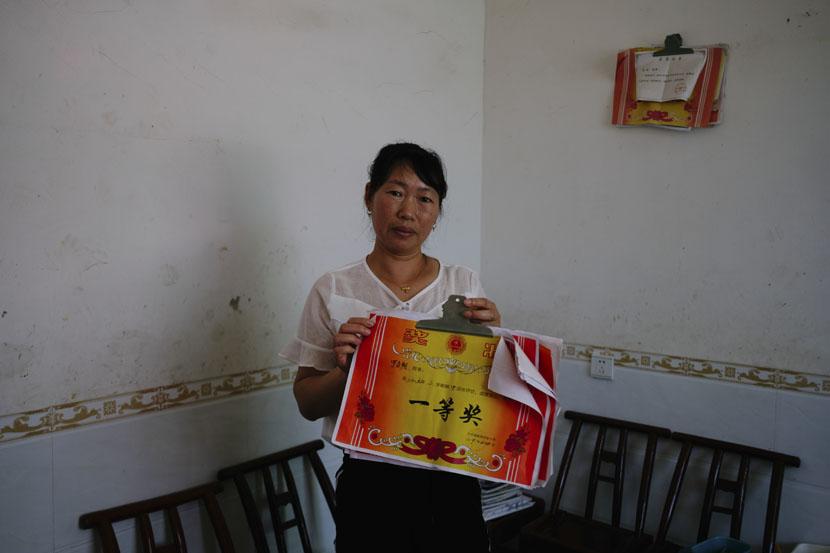 You Huanhong holds her son's academic certificates in Yangtian Village, Hunan province, June 4, 2019. Wu Huiyuan/Sixth Tone