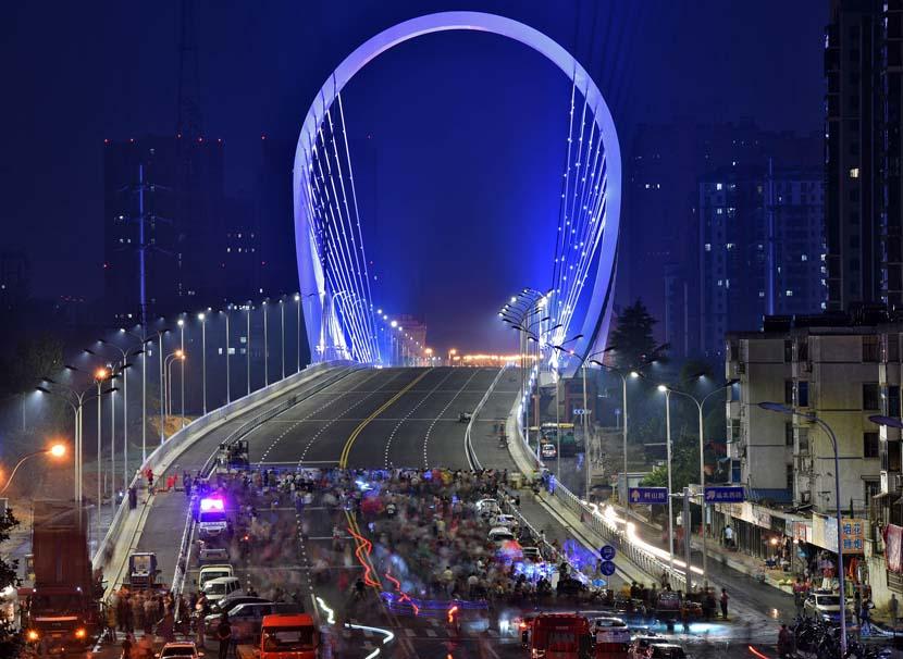 Residents take in a lightshow on a bridge over the Beijing-Hangzhou Grand Canal in Huai'an, Jiangsu province, June 24, 2019. He Jianghua/VCG