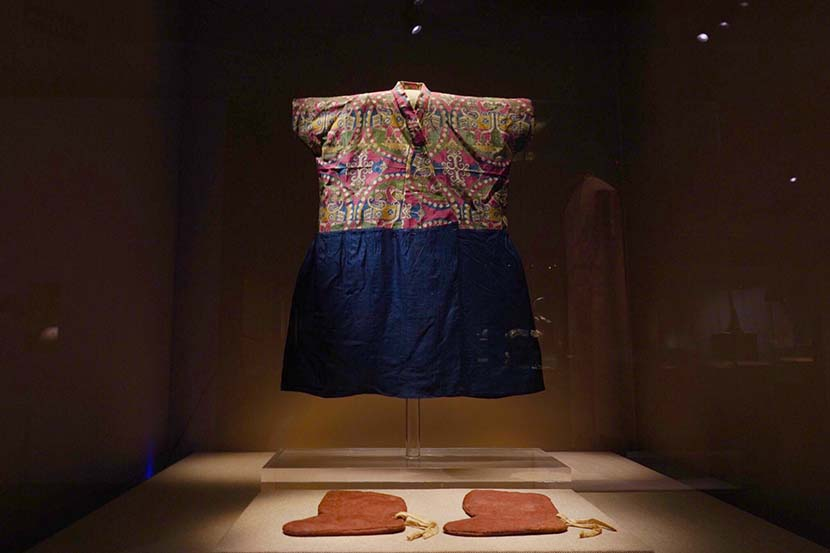 A child's silk garment and leather shoes are displayed at the Dunhuang Academy exhibition center in Dunhuang, Gansu province, July 2019. Courtesy of Dunhuang Academy
