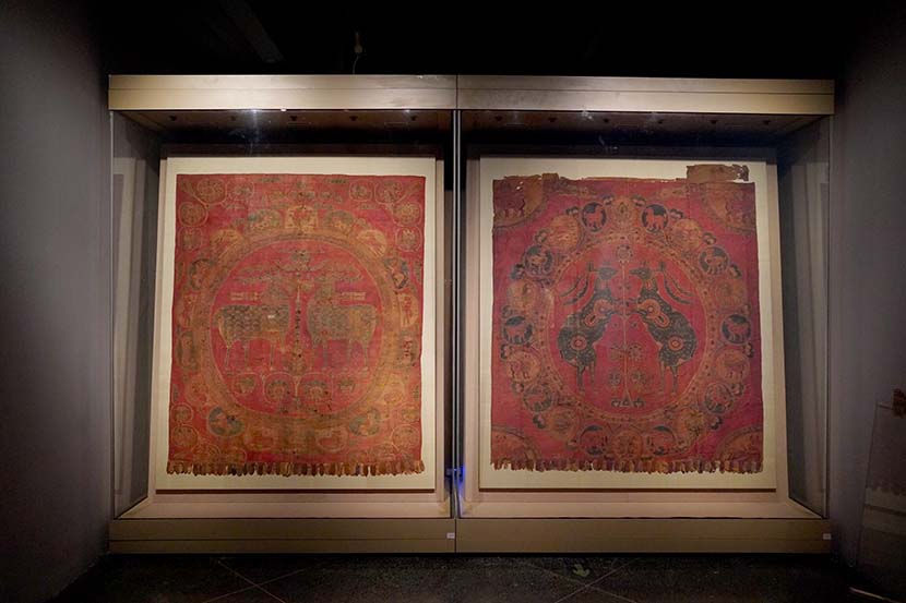 Silk brocades with large, circular panels and pearls in the upper-left corner of one are displayed at the Dunhuang Academy exhibition center in Dunhuang, Gansu province, July 2019. Courtesy of Dunhuang Academy