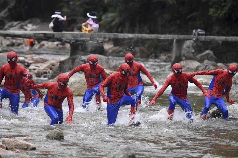 People dressed in Spider-Man suits run through a river during a race held at the Jiulong River National Forest Park in Chenzhou, Hunan province, July 4, 2019. Yang Huafeng/CNS/VCG