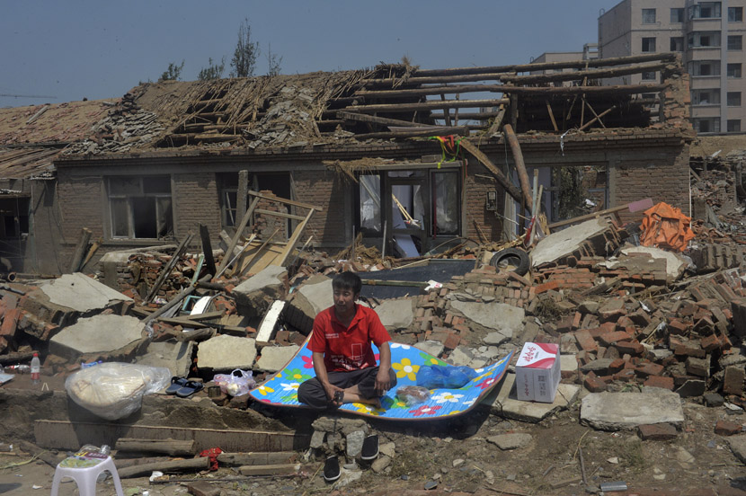 A man sits in front of a house that was destroyed by a tornado in Kaiyuan, Liaoning province, July 4, 2019. VCG