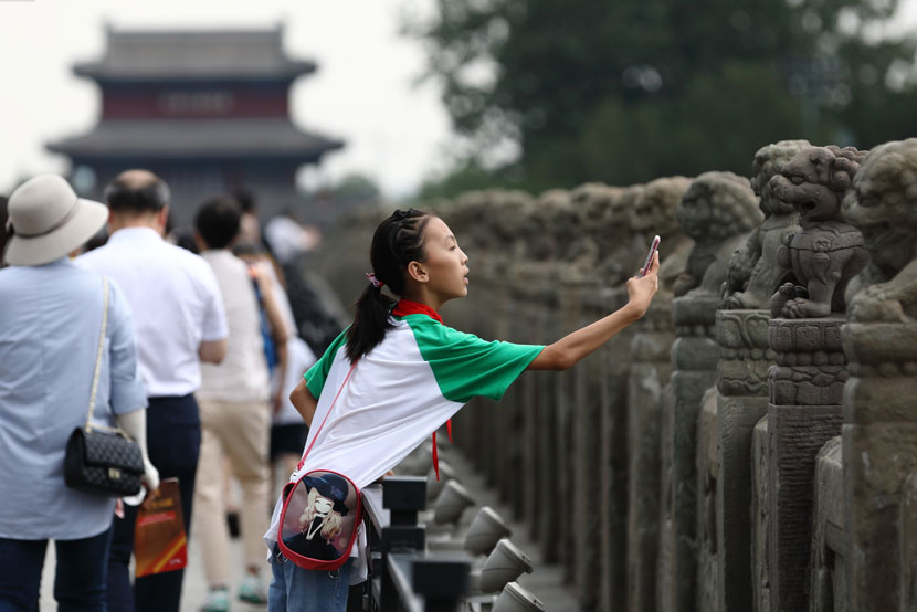 A girl photographs lion statues along the Marco Polo Bridge in Beijing, July 5, 2019. IC