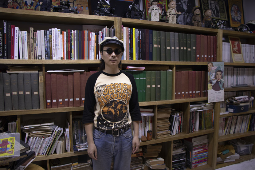 Feng Guangjun poses for a photo in front of his collection of old books and magazines at vintage shop Beachhunter in Hangzhou, Zhejiang province, June 18, 2019. Kenrick Davis/Sixth Tone