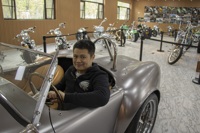 Zhang Xiaolei poses in a silver Shelby Cobra at Songsan Motors' Museum of Premium Vehicles in Beijing, April 22, 2019. Kenrick Davis/Sixth Tone
