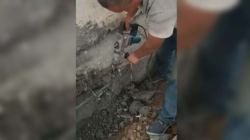 A video screenshot shows a construction worker demolishing the wall of a dormitory built with the allegedly substandard cement at Zhicheng Experimental School in Luyi County, Henan province. @中国青年报 on Weibo